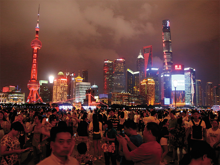 Cheerful crowds stroll the sea front in Pudong district of Shanghai, reminiscent of Hongkong's embankments; Shanghai is the third city in the world by population, and the world's largest seaport