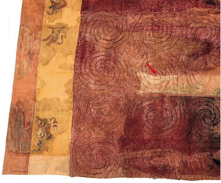 Шерстяной ковер, простеганный спиральным орнаментом, из погребальной камеры 20-го Ноин-Улинского кургана. На покрывающей ковер ткани – светлый зубчатый орнамент (мерлон) – показан красной стрелкой