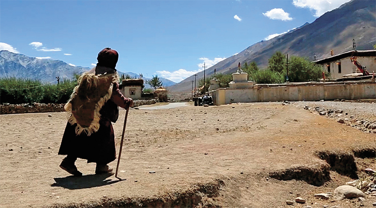 A village woman of Zanskar dressed in traditional clothes. She is walking towards the Sani Monastery