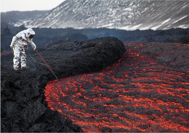 A volcanologist in an insulating suit measuring the temperature of the lava in a stream emerging from a lava duct in 1 kilometer from the active cinder cone of Tolbachik. March 2013. Photo by A. Belousov