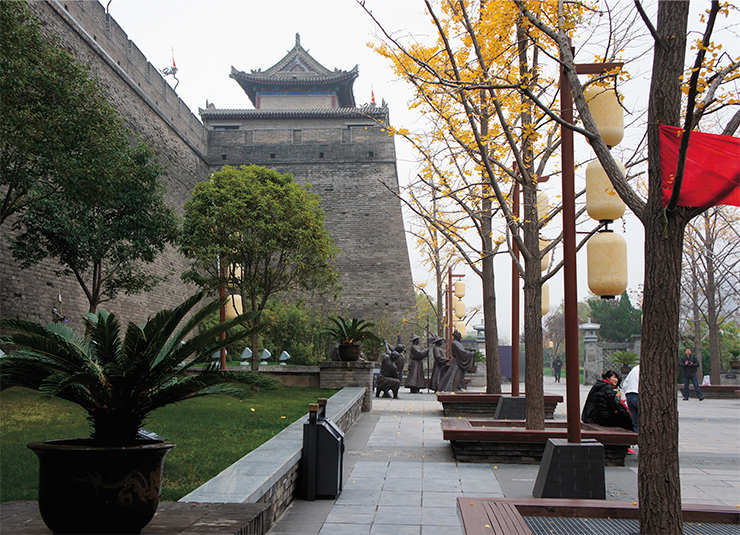 Xi'an, the center of the Shaanxi province, is over 30 centuries old; capitals of 13 Chinese dynasties, including Zhou, Qin, Han, Sui, and Tang, were located within its limits or in its nearest vicinities. The center of the city is surrounded by a 12-meter high, sturdy (up to 18 m wide at the base), well preserved fortress wall, built during Ming dynasty, over six centuries ago. At night, its merlons are highlighted by a chain of lights, and the gate arks are surrendered to pedestrians. The center of the square is occupied by the Drum Tower, built in the early Ming period (1380), named after the tradition of marking the end of each day with a roll of drums coming from the tower. The night-lights showcase the soft curves of its roofs and ornamented mouldings of its three levels against the dark sky, cleansing it from the marks left by the passing time and reviving the colors of the ancient structure