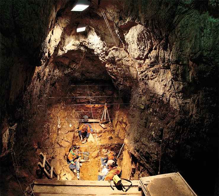 The total area of the cave is 270 m². Branching off from the central hall is a system of galleries: the eastern and southern narrow dark galleries go in the interior of a karst mass, where they are completely blocked by loose deposits. The third gallery leads to the site in front of the entrance. The photograph shows a dig in the eastern gallery of the Denisova Cave. Photographed by S. I. Zelensky