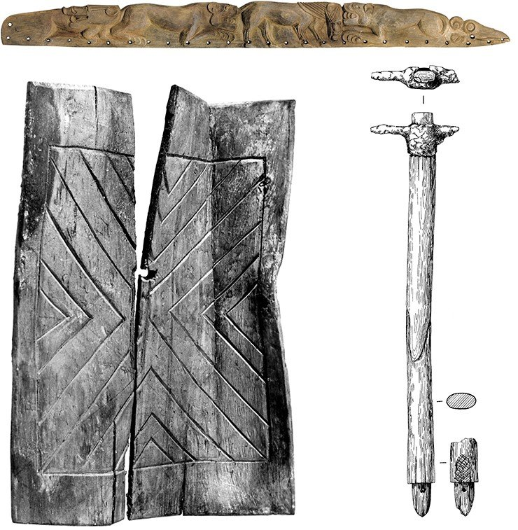 A wooden plate, a detail of the gorytos, with carved scenes of boars being torn by leopards, from the female burial (above). The defense weapons of Pazyryk riders is represented mainly by shields, which have been preserved in the non-looted Horse Compartments. A wooden shield (left). An iron ax hammer on a wooden handle from the female burial (right). Ak-Alakha 1 burial mound 1