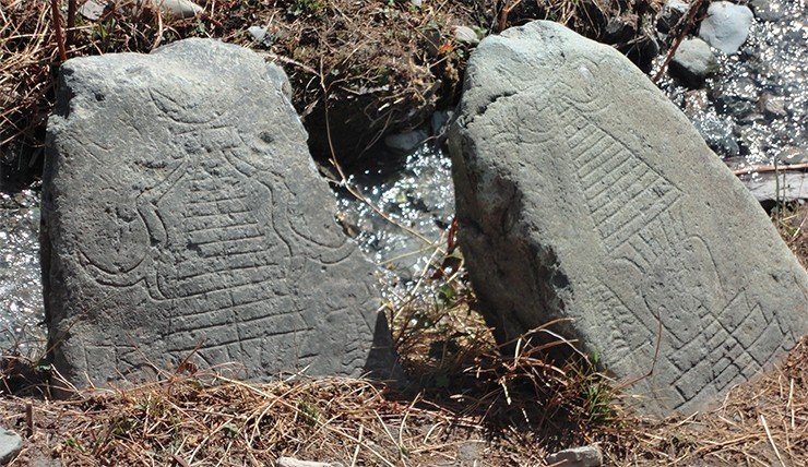 Stones with stupa images in a field near the village of Karsh